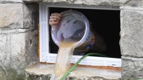 Ein Anwohnerin Hagen schöpft seinen überfluteten Keller leer.